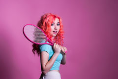 Girl with pink hair plays tennis on a pink background. Young girl with pink hair plays tennis on a pink background, space for text Stock Photo