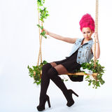 Girl with pink hair shakes on a swing Royalty Free Stock Photography