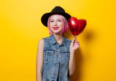 Girl with pink hair style with heart shape ballon. Portrait of young style hipster girl with pink hair style with heart shape balloon on yellow background. St Royalty Free Stock Photography