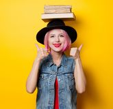 Girl with pink hairstyle holding books over head. Young style hipster girl with pink hairstyle holding books over head on yellow background Stock Photo