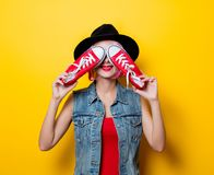 Girl with pink hairstyle and red gumshoes. Portrait of young style hipster girl with pink hairstyle and red gumshoes on yellow background Royalty Free Stock Photos