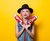 Girl with pink hairstyle and red gumshoes. Portrait of young style hipster girl with pink hairstyle and red gumshoes on yellow background Stock Photo