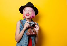 Girl with pink hairstyle with retro camera. Portrait of young style hipster girl with pink hairstyle with retro camera on yellow background Stock Photography
