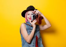 Girl with pink hairstyle with retro camera. Portrait of young style hipster girl with pink hairstyle with retro camera on yellow background Royalty Free Stock Photos