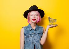 Girl with pink hairstyle with shopping cart. Portrait of young style hipster girl with pink hairstyle with shopping cart on yellow background Stock Photo