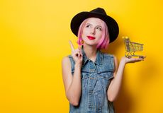 Girl with pink hairstyle with shopping cart. Portrait of young style hipster girl with pink hairstyle with shopping cart on yellow background Royalty Free Stock Image