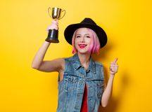 Girl with pink hairstyle with winner trophy. Portrait of young style hipster girl with pink hairstyle with winner trophy on yellow background Royalty Free Stock Photography