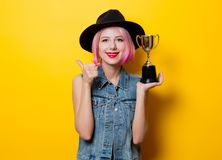 Girl with pink hairstyle with winner trophy. Portrait of young style hipster girl with pink hairstyle with winner trophy on yellow background Stock Images