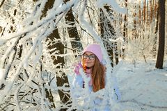 Girl in a pink hat drinking mulled wine in the winter in the forest. Royalty Free Stock Photo