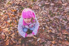 Girl in pink hat on the ground full of autumn leaves royalty free stock photos