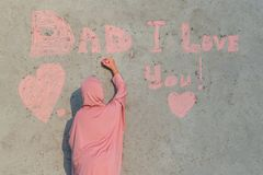 A girl in a pink hijab with chalk writes on the wall Dad I love you. Concept of happy father day royalty free stock images