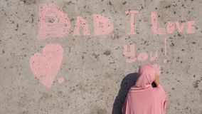 A girl in a pink hijab with chalk writes on the wall Dad I love you. stock footage