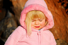 Girl with pink jacket. Toddler girl (3 years old) with blond hair, wearing pink jacket, has eyes closed stock images