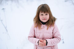 Girl in pink jacket gently freezing outside in  winter, snow, em Royalty Free Stock Photography
