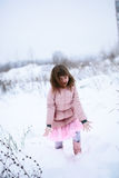 The girl in  pink jacket gently freezing play outside in the win. The girl in the pink jacket gently freezing play  outside in the winter, snow, emotions concept Stock Photo
