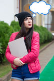 Girl in a pink jacket holding a laptop Royalty Free Stock Photography