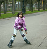 The girl in the pink jacket. Learns to ride on rollers Stock Image