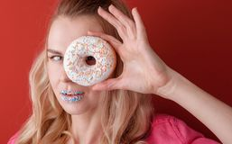 Girl in pink jacket on red background with donut in hands royalty free stock image