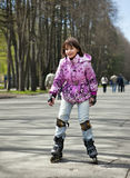 The girl in the pink jacket. Roller-skate Royalty Free Stock Photo
