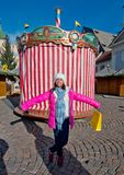 Little girl smiles in front of the old party carousel. Girl with pink jacket smiles happily in front of the old carousel with red and white striped party cloth Royalty Free Stock Photo