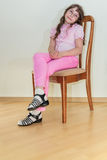Girl in pink jeans sitting on chair Stock Image