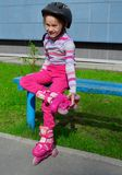 A girl in pink jeans and a striped sweatshirt in a roller helmet. On her head and rollers on her legs is sitting on a bench on a sunny summer day. Photo stock photo