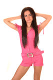 Girl in pink jumpsuit. A beautiful young woman in a pink jumpsuit standing in the studio and her Stock Photo