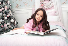 A girl in a pink knit cardigan in bed with a book Royalty Free Stock Photos