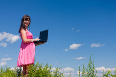 Girl in the pink with a laptop on the skyline Stock Photos