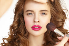 Girl with pink lips and curly hair put on makeup Royalty Free Stock Photography