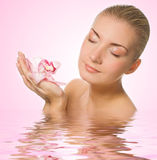 Girl with pink orchid Stock Image