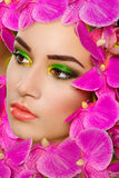 Girl with pink orchids in the face Stock Photos