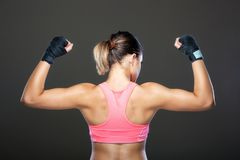Muscular girl portrait. Girl in pink outfit, showing muscles Royalty Free Stock Photo