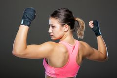 Muscular girl portrait. Girl in pink outfit, showing muscles Stock Photography