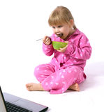 Girl in pink pajamas eating cereal Royalty Free Stock Images