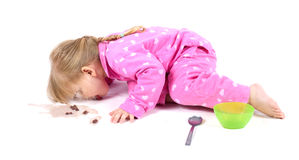 Girl in pink pajamas eating cereal Stock Photo