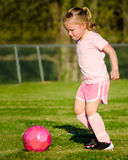 Girl in pink playing soccer on field Stock Photography