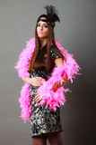 Girl pink plume and black feather on head. Carnival. Stock Photos