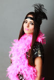 Girl pink plume and black feather on head. Carnival. Stock Photo