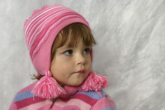 Girl with pink pom-pons. Kid wearing pink striped jumper and a cap Stock Photo