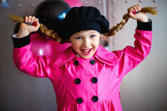 The girl in a pink raincoat Stock Image
