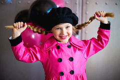 The girl in a pink raincoat Stock Images