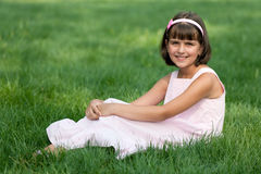 Girl in pink resting on the green grass Royalty Free Stock Photos