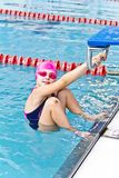 Girl in pink rubber hat. Photo of jumping girl in swimming pool stock images