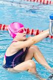 Girl in pink rubber hat. Photo of jumping girl in swimming pool royalty free stock image