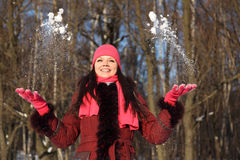 Girl in pink scarf and hat throwing up snow Royalty Free Stock Photography