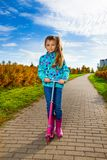 Girl with pink scooter. Nice cute little girl ride a fancy pink scooter in the autumn park Royalty Free Stock Photography