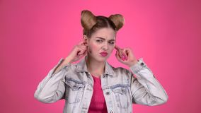 Girl screams, she does not want to hear anything. Pink background. Slow motion