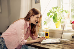 Girl in pink shirt at home talking on phone, communicating on laptop. Royalty Free Stock Image