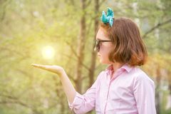 Girl in a pink shirt and sunglasses in the nature holding a sun royalty free stock photo